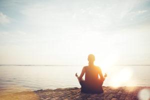 Kvinna mediterar i solnedgången vid sjö